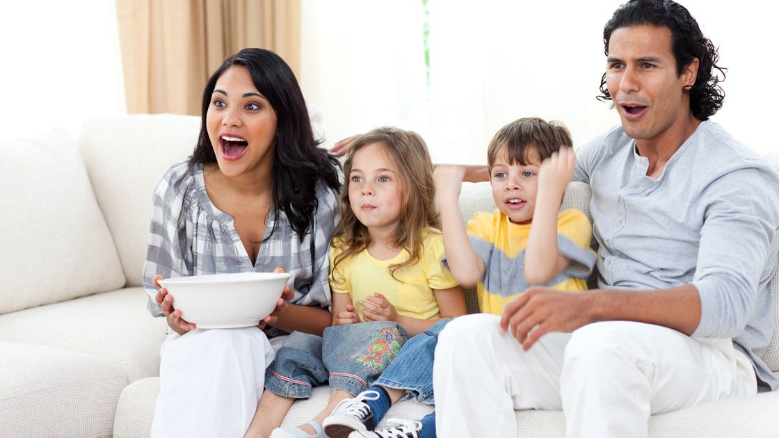 Cute siblings watching TV with their parents