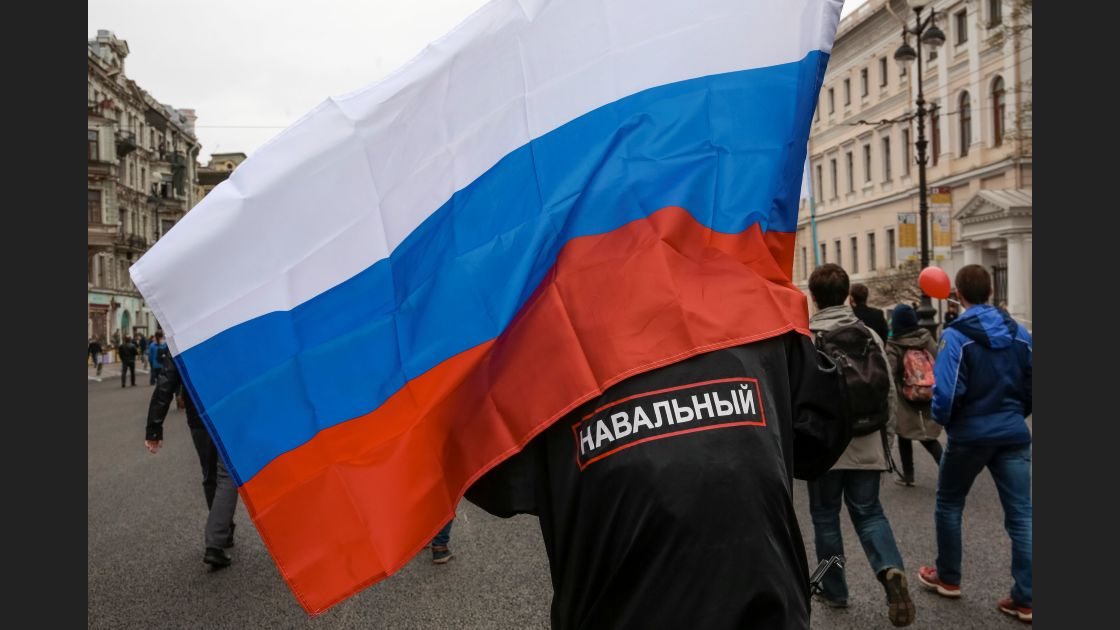 A supporter of Russian opposition leader Alexei Navalny carries a national flag as he attends a protest rally ahead of President Vladimir Putin