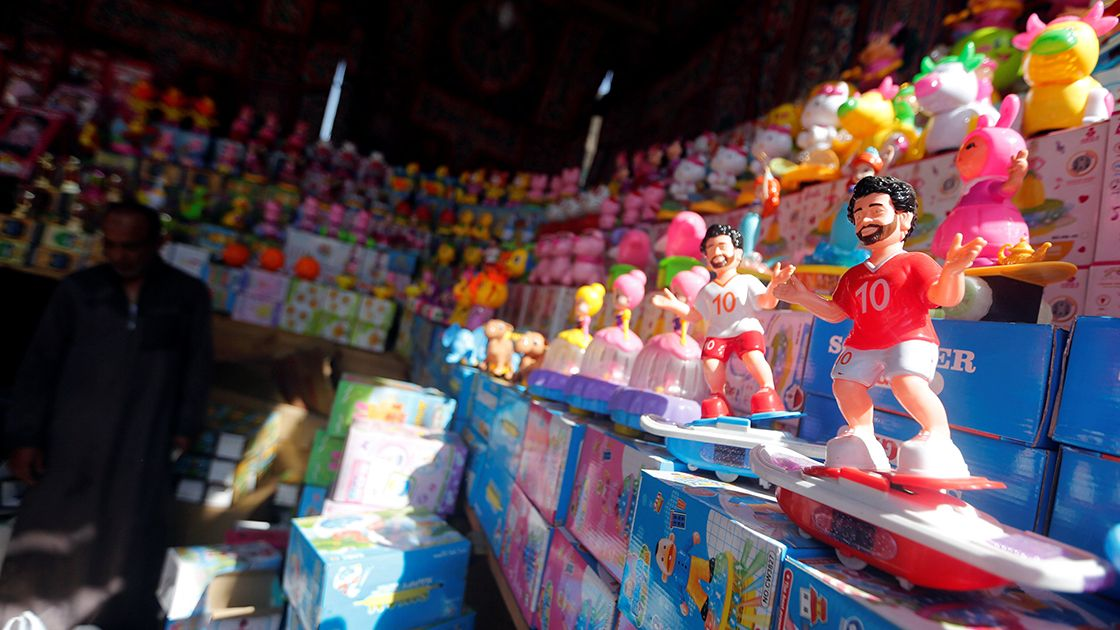 A seller waits for the customers near the toys depicting Liverpool