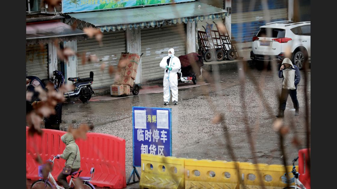 FILE PHOTO: A worker in a protective suit is seen at the closed seafood market in Wuhan