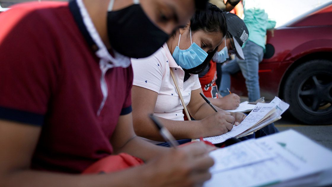 Job seekers fill out job application forms for assembly factories as the coronavirus disease (COVID-19) outbreak continues in Ciudad Juarez